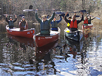 group of students canoeing on lake