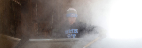 student boiling sap into maple syrup on NMH farm