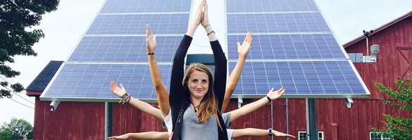 students standing in front of solar panels near campus barn