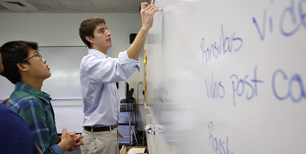 Teacher writing on whiteboard at co-ed boarding school near boston