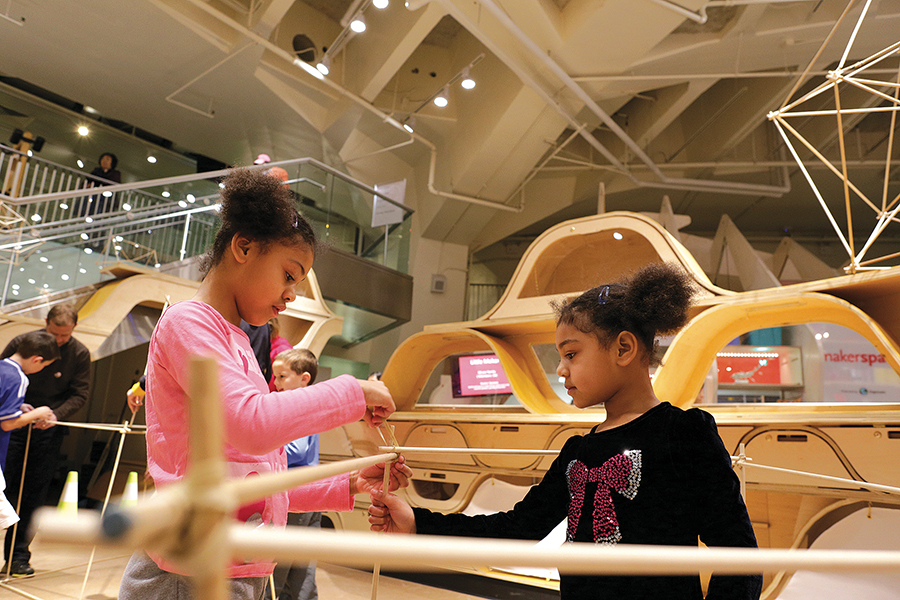 2 young girls playing with interactive display