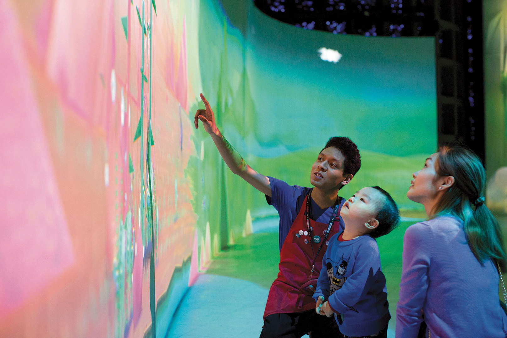 A docent points out a feature of a colorful mural to a child.