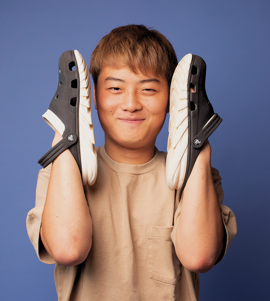 Yudai has hands in his crocs, and is framing his happy face with them.