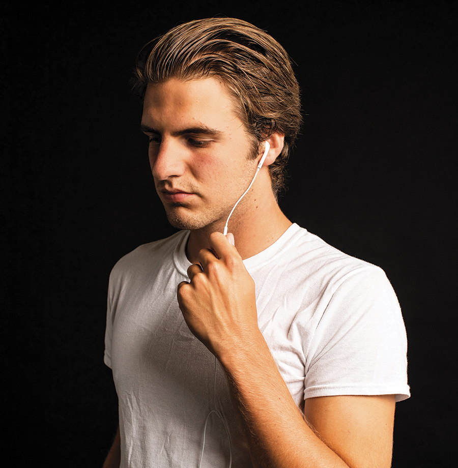 Marcus wearing a white T-shirt looking pensive with white earbuds in his ear