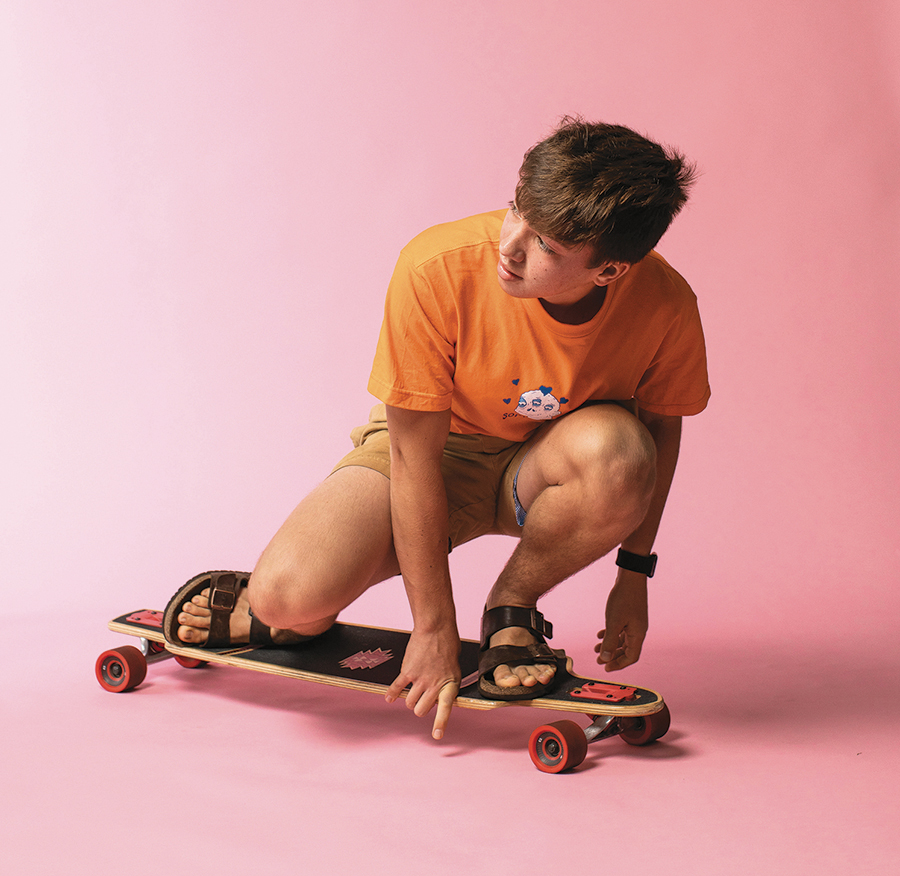 Alex is looking back over his shoulder as he crouches down on his skateboard